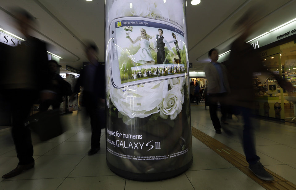 Photo -   People walk past an advertisement poster of a Samsung Electronics Co. product at a subway station in Seoul, South Korea, Friday, Oct. 26, 2012. Samsung's third-quarter net profit nearly doubled over a year earlier to a record high propelled by strong sales of Galaxy phones that helped widen its lead over rivals. (AP Photo/Lee Jin-man)