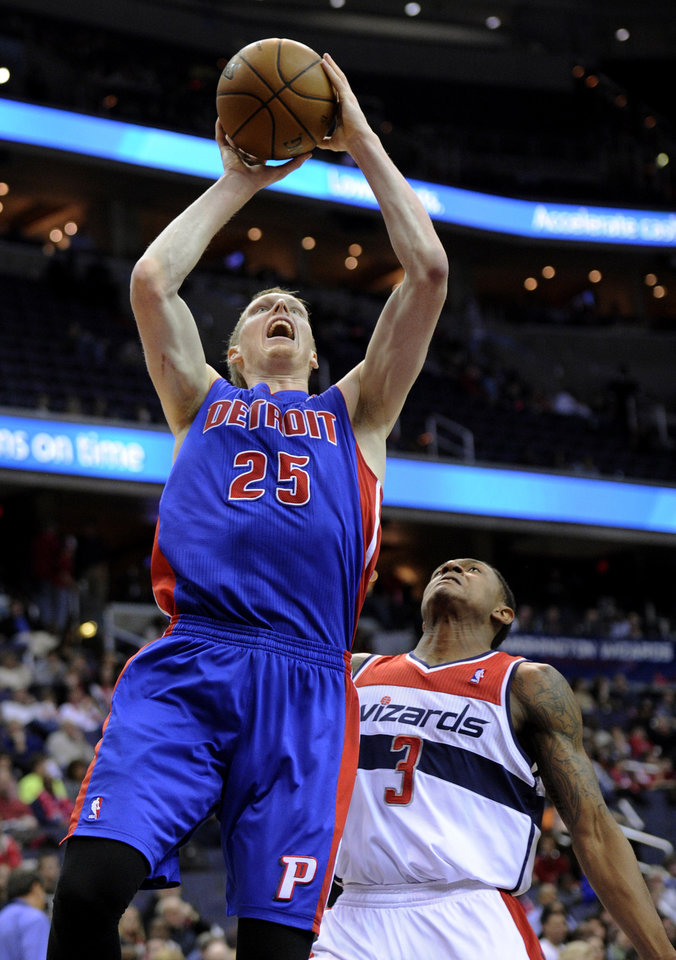 Photo - Detroit Pistons forward Kyle Singler (25) goes to the basket against Washington Wizards guard Bradley Beal (3) during the first half of an NBA basketball game, Saturday, Dec. 22, 2012, in Washington. (AP Photo/Nick Wass)