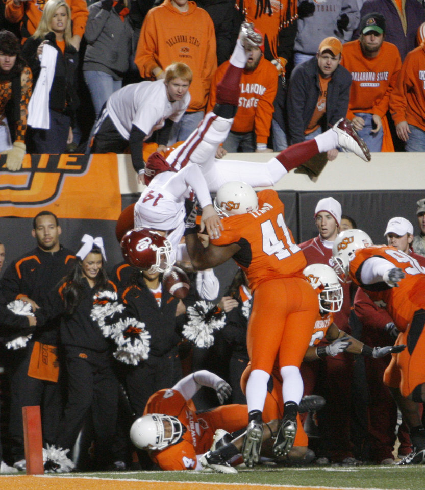 Photo - OU quarterback Sam Bradford leaps over Orie Lemon during the second half of the college football game between the University of Oklahoma Sooners (OU) and Oklahoma State University Cowboys (OSU) at Boone Pickens Stadium on Saturday, Nov. 29, 2008, in Stillwater, Okla. STAFF PHOTO BY CHRIS LANDSBERGER