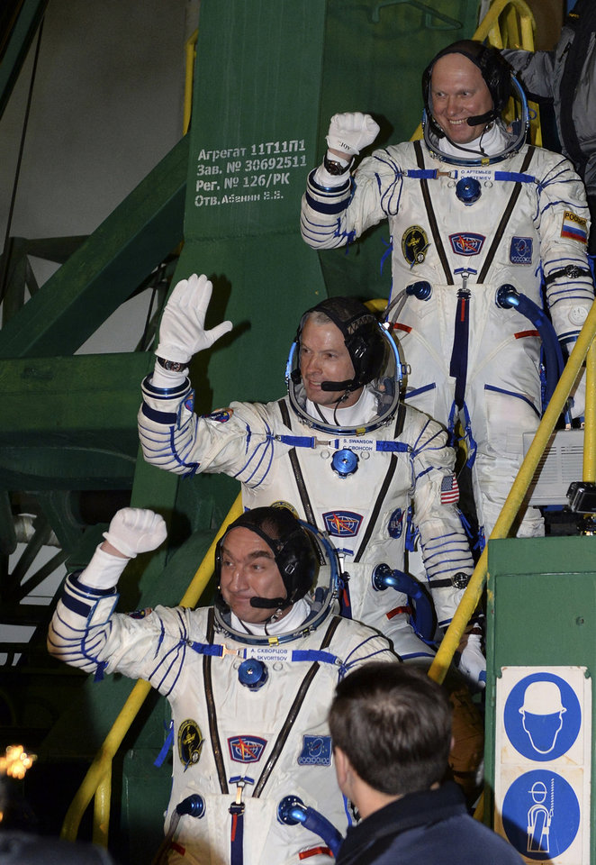 Photo - U.S. astronaut Steven Swanson, center, Russian cosmonauts Alexander Skvortsov, bottom, and Oleg Artemyev, crew members of the mission to the International Space Station (ISS) gesture prior the launch of Soyuz-FG rocket at the Russian leased Baikonur cosmodrome, Kazakhstan, Wednesday, March 26, 2014. (AP Photo/Vasily Maximov, Pool)