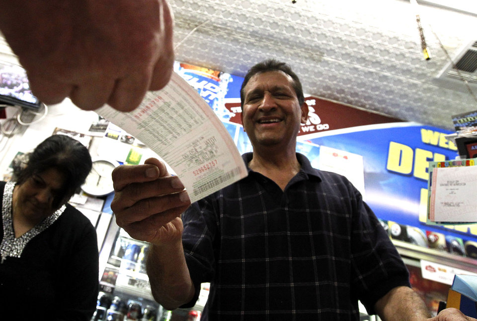 Photo - As he hands over a customer's lottery ticket, Keith Ganatra, right, and his wife Anita Ganatra, left, owners of the Del Monte Market, help the long line of customers inside their store waiting to buy Powerball lottery tickets Wednesday, Nov. 28, 2012, in Phoenix. There has been no Powerball winner since Oct. 6, and the jackpot has already reached a record level for the game of over $550 million. (AP Photo/Ross D. Franklin)