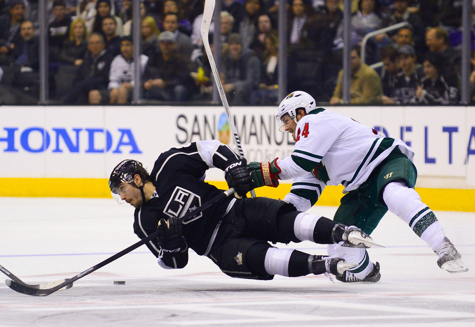 Photo - Los Angeles Kings defenseman Drew Doughty, left, stays on the puck as he battles Minnesota Wild left wing Matt Cooke (24) for it during the second period of an NHL hockey game, Monday, March 31, 2014, in Los Angeles. (AP Photo/Gus Ruelas)