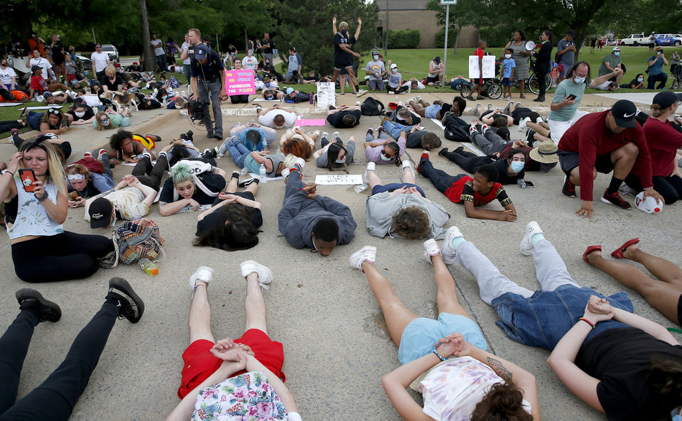 Photo - Protesters lie on the ground at the Norman Police Department in Norman, Okla.  Tuesday, June 2, 2020.  [Sarah Phipps/The Oklahoman]