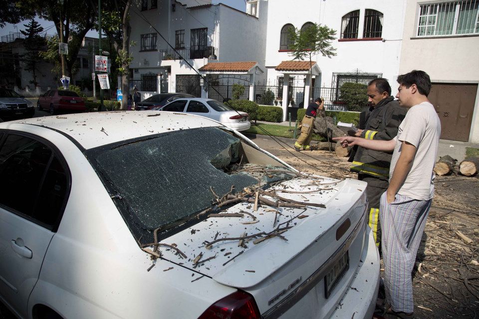 Photo - A man talks with a fireman after a tree fell on his car at the Narvarte neighborhood after a strong earthquake jolted Mexico City, Friday, April 18, 2014. The powerful magnitude-7.2 earthquake shook central and southern Mexico but there were no early reports of major damage or casualties. (AP Photo/Eduardo Verdugo)