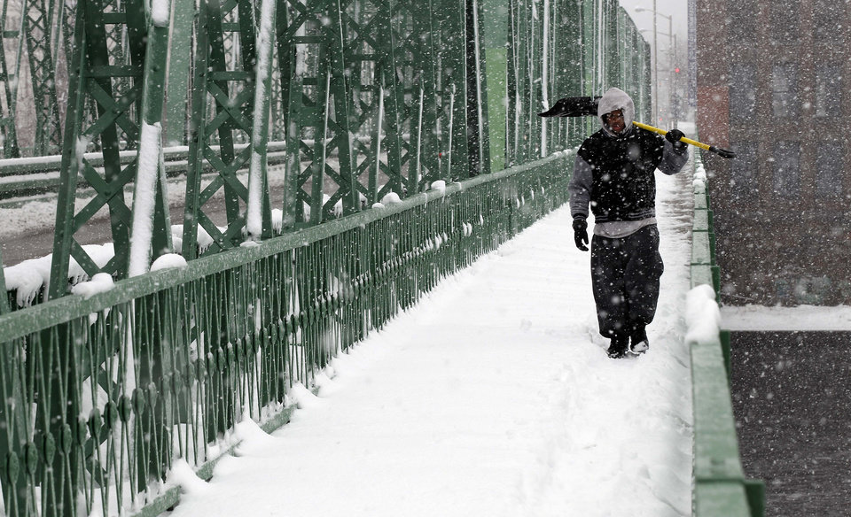 Photo - Jeffrey Colon carries his shovel across a bridge to help friends shovel out during a winter storm in Lawrence, Mass. Tuesday, March 19, 2013.  Winter went out with a blast in the Northeast on Tuesday, snow and sleet delaying the start of school in some areas and making the morning commute an icy, slippery mess a day before spring starts. The nasty weather led some schools in upstate New York, Massachusetts and Connecticut to close, adding a few more snow days to school calendars. (AP Photo/Winslow Townson)