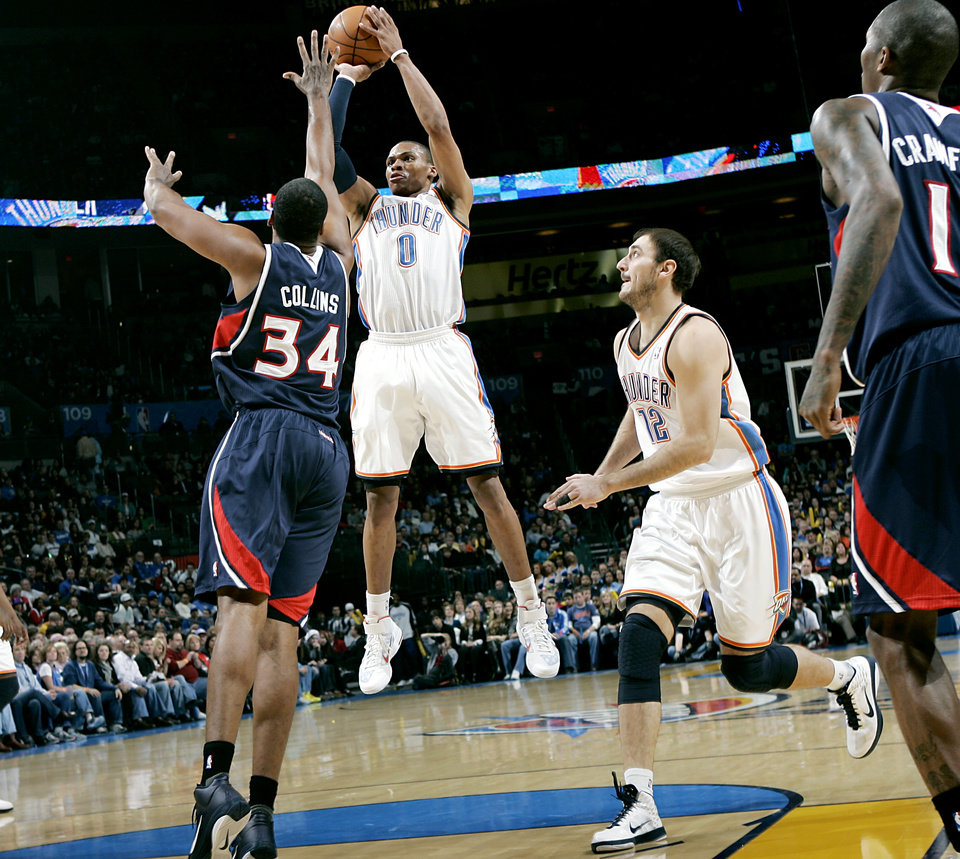 Photo - Oklahoma City's Nenad Krstic watches teammate Russel Westbrook put a shot over Atlanta's Jason Collins during their NBA basketball game at the OKC Arena in Oklahoma City on Friday, Dec. 31, 2010. Photo by John Clanton, The Oklahoman