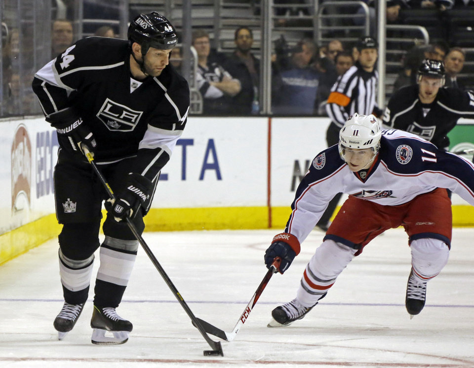 Photo - Los Angeles Kings defenseman Robyn Regehr (44) and Columbus Blue Jackets left wing Matt Calvert (11) battle for the puck in the first period of an NHL hockey game in Los Angeles, Thursday, April 18, 2013. (AP Photo/Reed Saxon)