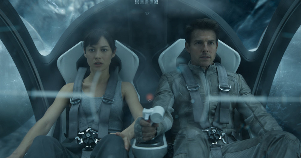 "This film publicity image released by Universal Pictures shows Olga Kurylenko, left, and Tom Cruise in a scene from ""Oblivion."" (AP Photo/Universal Pictures)"