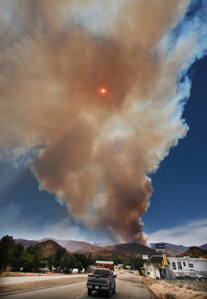 Photo - The Shirley Fire kicks up  smoke with the sun in the center  in Wofford Heights, Calif., Sunday, June 15, 2014.   The Forest Service reported Sunday morning that the amount of acreage charred by the fire burning about 30 miles northeast of Bakersfield more than doubled overnight to 2.8 square miles.   The Kern County Sheriff's Office has called for the evacuation of about 500 homes in the Wofford Heights area. (AP photo/The Bakersfield Californian, Casey Christie)   MANDATORY CREDIT; MAGS OUT; NO SALES; ONLINE OUT; TV OUT