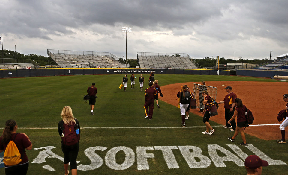 Photo - COLLEGE SOFTBALL: As storms move into the area the Arizona State University softball team leaves the field the day before the opening game of the Women's College World Series at ASA Hall of Fame Stadium in Oklahoma City, Wednesday, May 29, 2013. Photo by Bryan Terry, The Oklahoman
