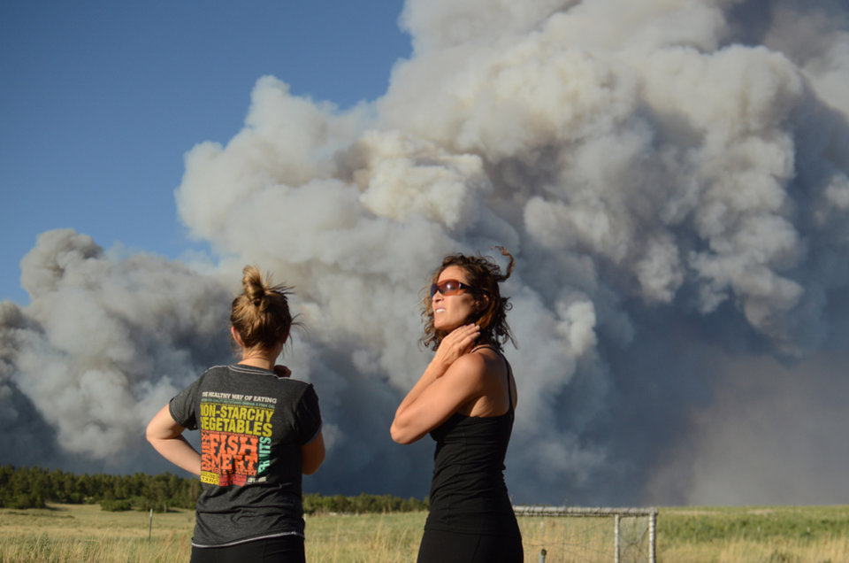 Photo - The Black Forest Fire burns northeast of Colorado Springs, Colo., Tuesday, June 11, 2013, as nearby residents Amy O'Connor, left, and Nathalie Bartleson watch it creep toward the tree line. The fire consumed an estimated 7,500 acres, damaged 40-60 structures and forced the evacuation of thousands of people. (AP Photo/Bryan Oller)