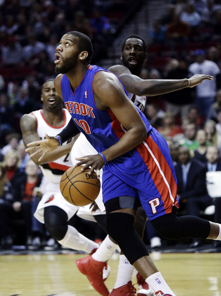 Detroit Pistons center Greg Monroe, middle, drives to the basket past Portland Trail Blazers center J.J. Hickson, right, and guard Wesley Matthews during the first quarter of an NBA basketball game in Portland, Ore., Saturday, March 16, 2013. (AP Photo/Don Ryan)