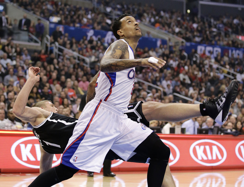 Photo - Los Angeles Clippers' Matt Barnes, front, fouls Brooklyn Nets' Mason Plumlee during the first half of an NBA basketball game on Saturday, Nov. 16, 2013, in Los Angeles. (AP Photo/Jae C. Hong)