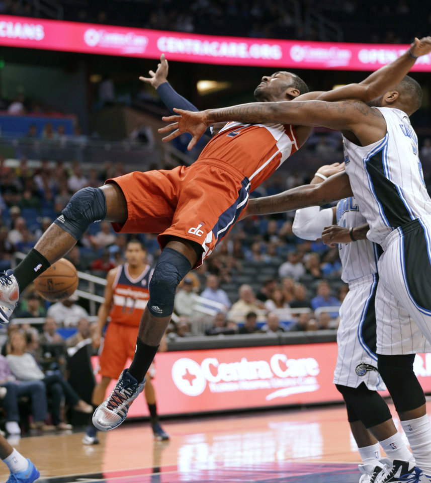 Washington Wizards\' John Wall, left, is fouled on a shot by Orlando Magic\'s Kyle O\'Quinn, right, during the first half of an NBA basketball game, Friday, March 29, 2013, in Orlando, Fla. (AP Photo/John Raoux)