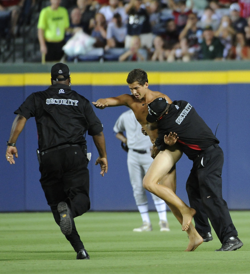 Photo - Time is halted as a streaker is confronted by Atlanta Braves security personnel during the sixth inning of a baseball game against the Oakland Athletics Saturday, Aug. 16, 2014, in Atlanta. (AP Photo/David Tulis)