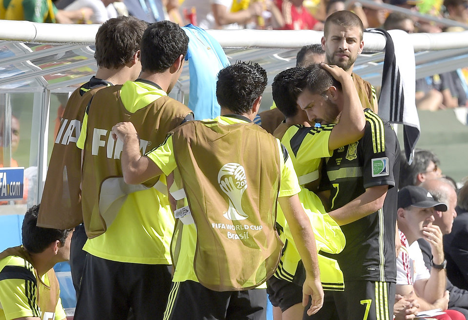 Photo - Spain's David Villa, right, is comforted by teammates as he leaves the pitch during the group B World Cup soccer match between Australia and Spain at the Arena da Baixada in Curitiba, Brazil, Monday, June 23, 2014. (AP Photo/Manu Fernandez)