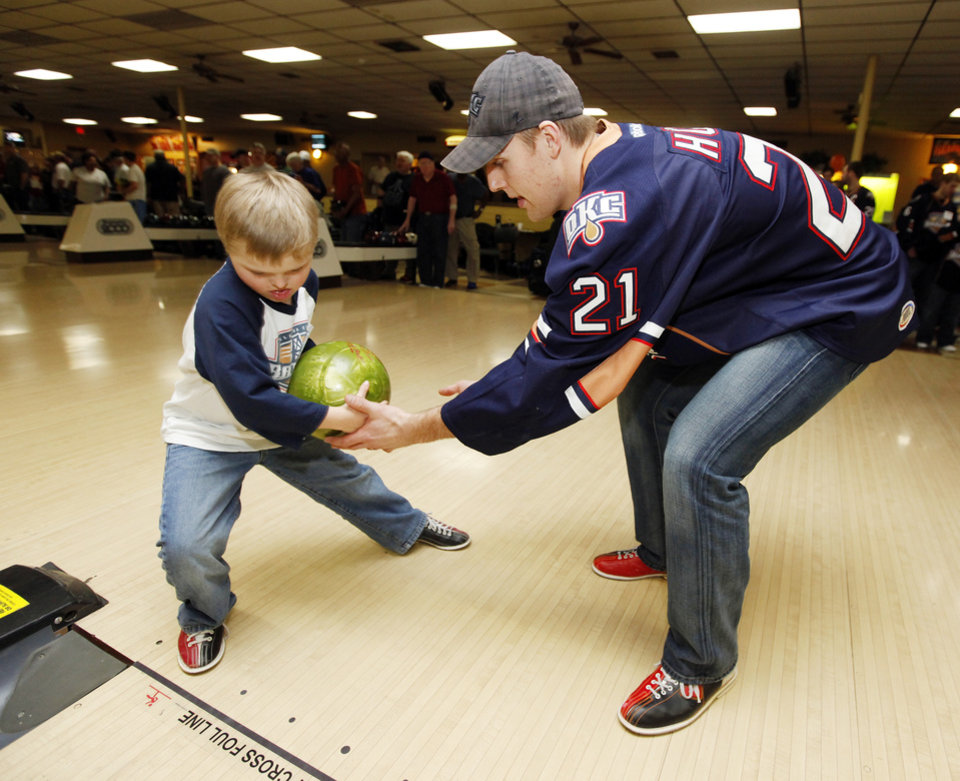 Photo - CHILD / CHILDREN / KIDS: Barons player Tanner House (21) helps Reis Wathen, 9, bowl during the Barons Buddies event with the Oklahoma City Barons AHL hockey team and Special Olympians at AMF Sunny Lanes bowling alley in Del City, Okla., Wednesday, Jan. 25, 2012. Photo by Nate Billings, The Oklahoman