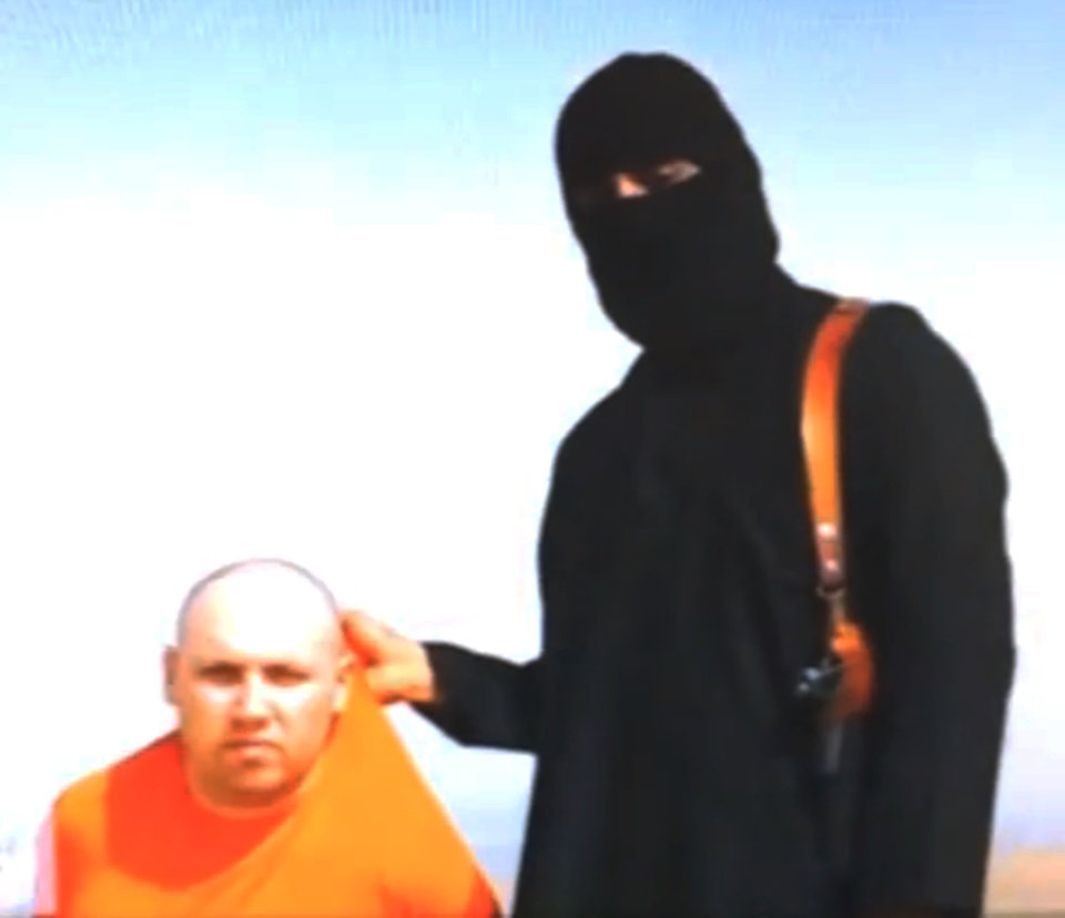 Photo - FILE - In this  file still image from an undated video released by Islamic State militants on Tuesday, Aug. 19, 2014, purports to show journalist Steven Sotloff being held by the militant group. An Internet video purporting to show the beheading of U.S. journalist Sotloff by the Islamic State group was posted online Tuesday, a beheading described as retribution for continued U.S. airstrikes in Iraq. (AP Photo, File)