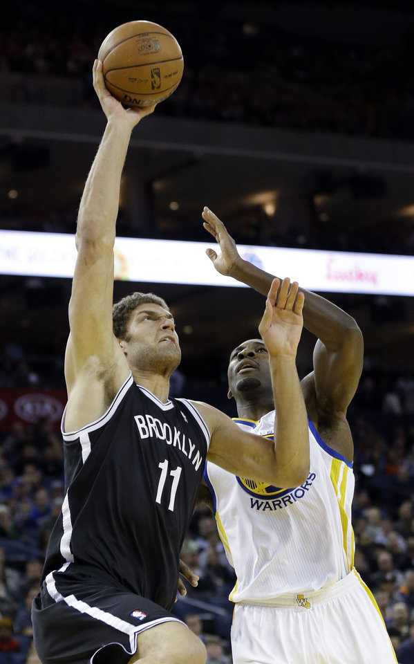 Photo -   Brooklyn Nets' Brook Lopez (11) shoots next to Golden State Warriors' Festus Ezeli (31) during the first half of an NBA basketball game in Oakland, Calif., Wednesday, Nov. 21, 2012. (AP Photo/Marcio Jose Sanchez)