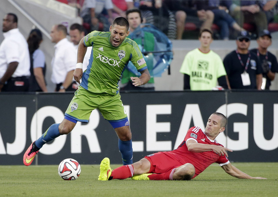 Photo - Seattle Sounders forward Clint Dempsey, left, is defended by San Jose Earthquakes midfielder Sam Cronin during the first half of an MLS soccer match Saturday, Aug. 2, 2014, in Santa Clara, Calif. (AP Photo/Marcio Jose Sanchez)