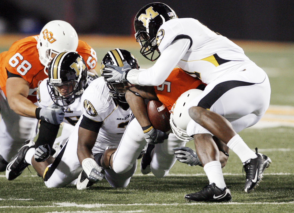 Photo - Keith Toston takes on three defenders during the second half of the college football game between Oklahoma State University (OSU) and the University of Missouri (MU) at Boone Pickens Stadium in Stillwater, Okla. Saturday, Oct. 17, 2009.  Photo by Steve Sisney, The Oklahoman