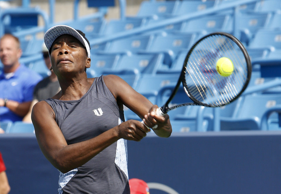 Photo - Venus Williams returns a volley to Lucie Safarova, from Czech Republic, during a first round match at the Western & Southern Open tennis tournament, Tuesday, Aug. 12, 2014, in Mason, Ohio. (AP Photo/David Kohl)