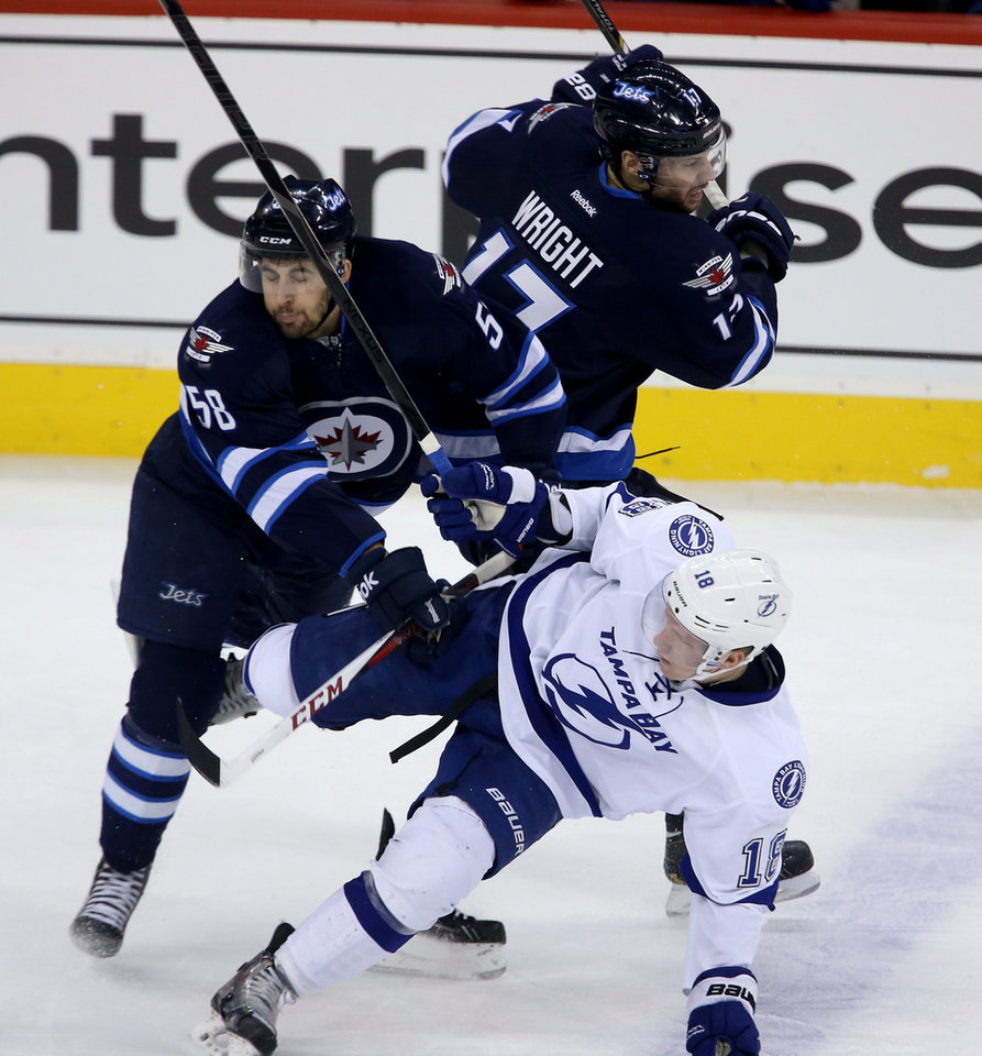 Photo - Winnipeg Jets' Eric O'Dell (58) and James Wright (17) collide with Tampa Bay Lightning's Ondrej Palat (18) during the first period of an NHL hockey game Tuesday, Jan. 7, 2014, in Winnipeg, Manitoba. (AP Photo/The Canadian Press, Trevor Hagan)