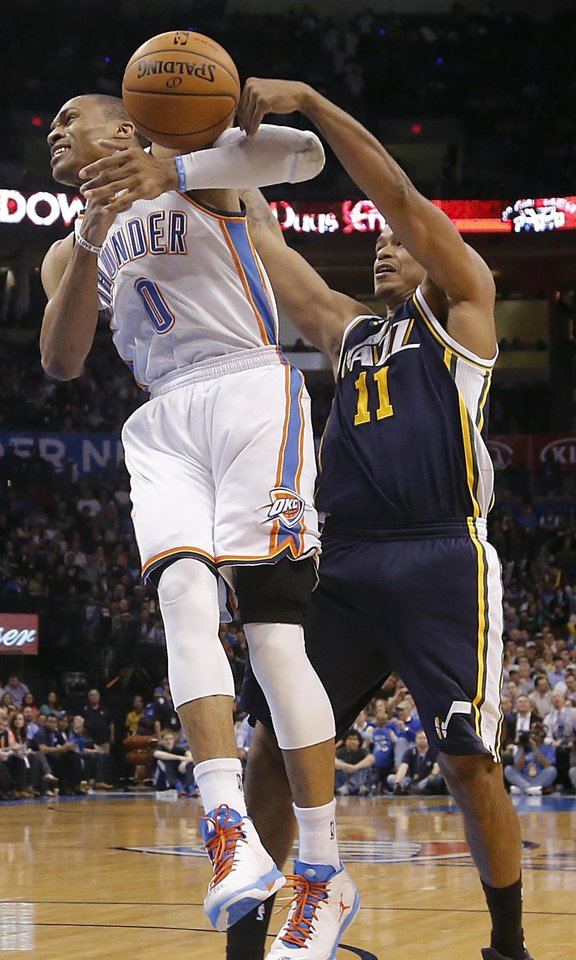 Photo - Oklahoma City Thunder's Russell Westbrook (0) looses the ball while defended by Utah Jazz's Earl Watson (11) during the NBA basketball game between the Oklahoma City Thunder and the Utah Jazz at Chesapeake Energy Arena on Wednesday, March 13, 2013, in Oklahoma City, Okla. Photo by Chris Landsberger, The Oklahoman