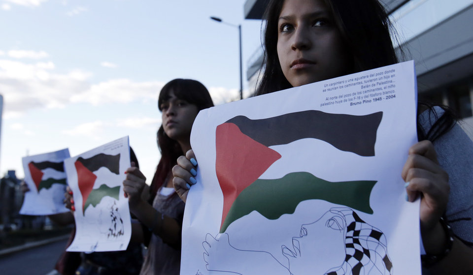Photo - Protesters hold posters designed with images of the Palestinian flag during a demonstration to show support for Palestinians in front of Israel's diplomatic headquarters, in Quito, Ecuador, Friday, July 18, 2014. Israeli troops pushed deeper into Gaza on Friday to destroy rocket launching sites and tunnels, firing volleys of tank shells and clashing with Palestinian fighters in a high-stakes ground offensive meant to weaken the enclave's Hamas rulers.  (AP Photo/Dolores Ochoa)