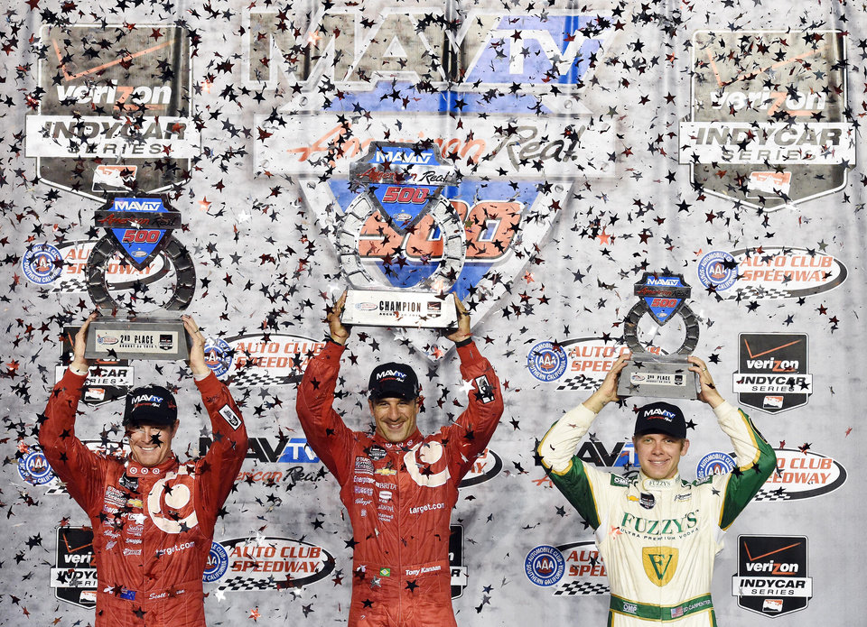 Photo - Tony Kanaan (center) holds the winners trophy along side teammate and second place finisher Scott Dixon (left), with third place finisher Ed Carpenter (right) following the IndyCar Series season final 500 mile auto race Saturday, Aug. 30, 2014, at Auto Club Speedway, in Fontana, Calif. (AP Photo/Will Lester)