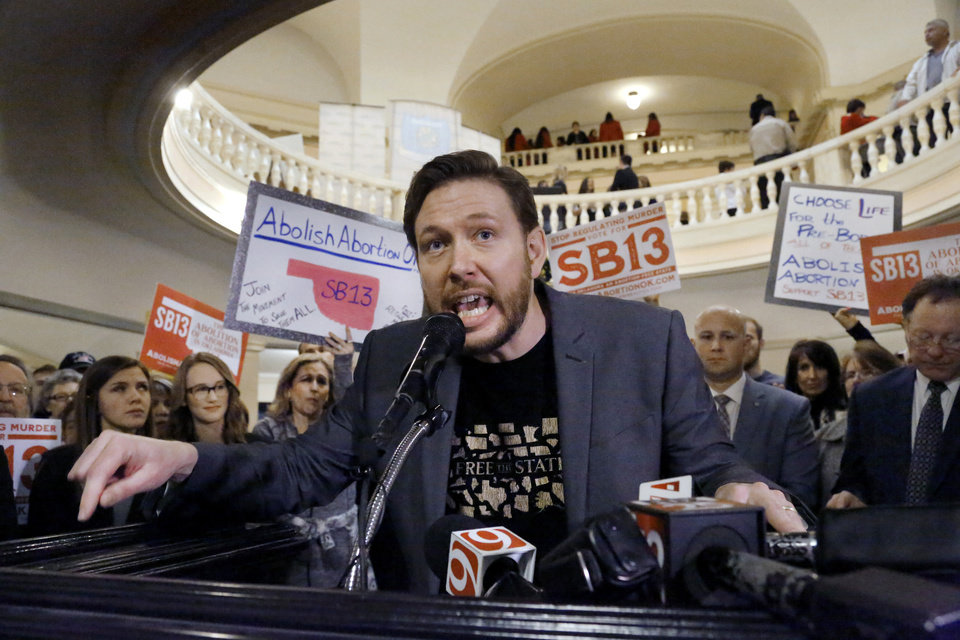 Photo - Josh Malone encourages rally participants to remain committed to their cause. A vocal crowd of about 400 pro-life activists carried signs condemning abortion, calling it an act of murder,  and cheered a lengthy slate of speakers who urged the group to stand and fight  for the repeal of legalized abortion in America during a rally on the first floor of the state Capitol Tuesday morning, Feb. 12, 2019.  Oklahomans opposing abortion have expressed a new energy with a Trump presidency and the belief the U.S. Supreme Court has shifted. Ultimately, their goal, through legal channels, is  an overturning of landmark Supreme Court decision, Roe v. Wade. Currently, there are several anti-abortion bills that activists are looking to promote. Senate Bill 13 would make abortion a felony homicide and many who gathered at the Capitol said they wanted lawmakers to support the bill, even if it resulted in a legal challenge.  Gov. Kevin Stitt reaffirmed his support for anti-abortion legislation at a Capitol rally last week.  Photo by Jim Beckel, The Oklahoman.