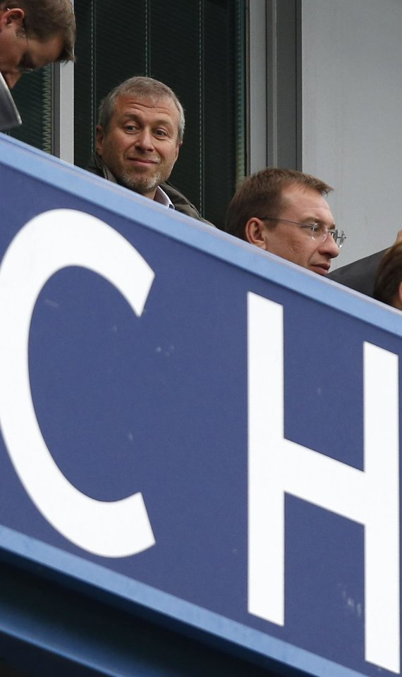 Photo - Chelsea's owner Roman Abramovich, left looks down to the pitch as he wait for the English Premier League soccer match between Chelsea and Fulham to begin at Stamford Bridge, London, Saturday, Sept. 21, 2013. (AP Photo/Sang Tan)