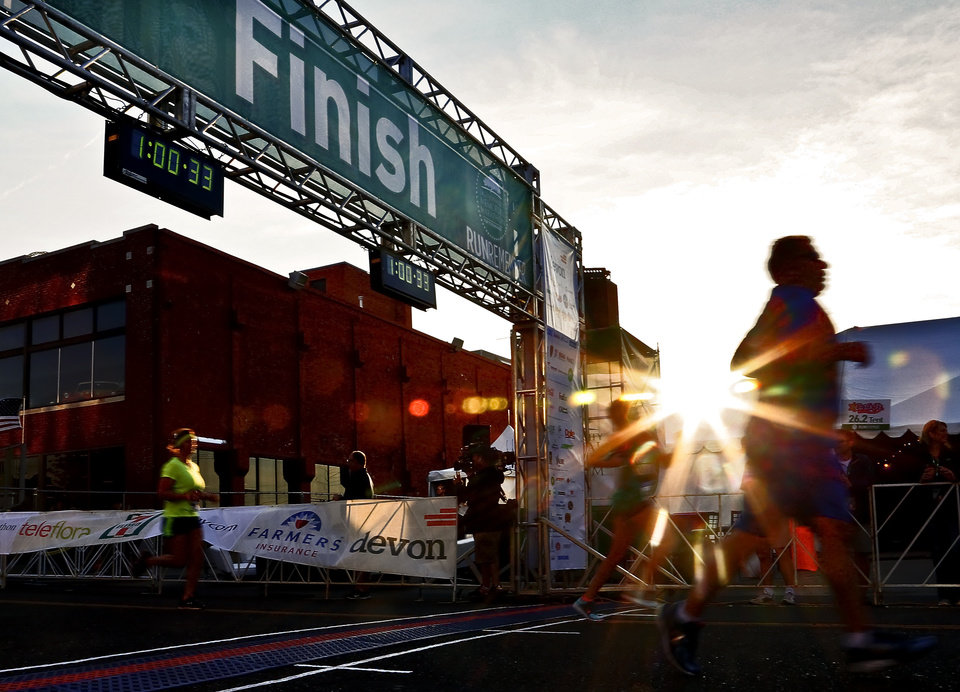 Photo - A runner crosses the finish line in the 5K during the Oklahoma Memorial Marathon in Oklahoma City, Okla. on Sunday, April 24, 2016.   Photo by Chris Landsberger, The Oklahoman