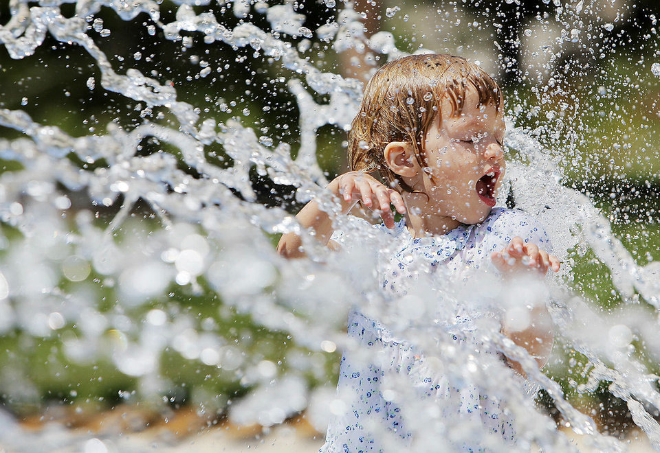 Photo - Lucy Baker, 2, keeps cool Monday by playing in a water fountain at the Myriad Botanical Gardens in Oklahoma City. Photo by Nate Billings, The Oklahoman