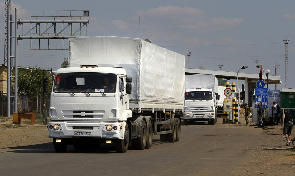 Photo - The first trucks of the aid convoy pass the border post at Izvaryne, eastern Ukraine, Friday, Aug. 22, 2014. The first trucks in a Russian aid convoy crossed into eastern Ukraine on Friday, seemingly without Kiev's approval, after more than a week's delay amid suspicions the mission was being used as a cover for an invasion by Moscow. (AP Photo/Sergei Grits)