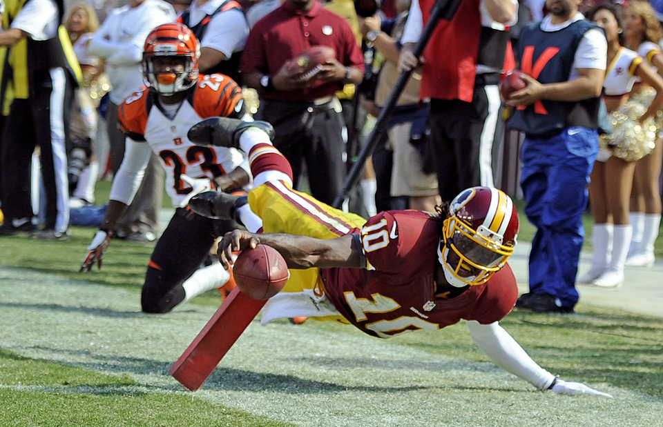Photo -   Washington Redskins quarterback Robert Griffin III is knocked out of boards shy of the goal line during the second half of an NFL football game against Cincinnati Bengals in Landover, Md., Sunday, Sept. 23, 2012. (AP Photo/Nick Wass)