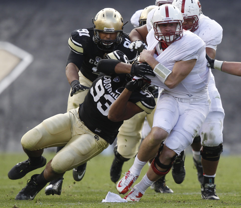Stanford quarterback Kevin Hogan, right, is tackled by Colorado defensive linemen Samson Kafovau, front left, during the third quarter of Stanford's 48-0 victory in an NCAA college football game in Boulder, Colo., on Saturday, Nov. 3, 2012. (AP Photo/David Zalubowski)