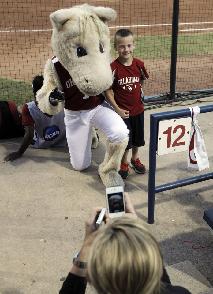 Seven-year-old Cade Lorenz has his photo taken with Boomer, the Oklahoma mascot, by Crystal Lorenz at the WCWS Finals second game where Oklahoma defeated Tennessee 4-0 on June 4, 2013 to win the NCAA championship. Photo by KT KING, The Oklahoman
