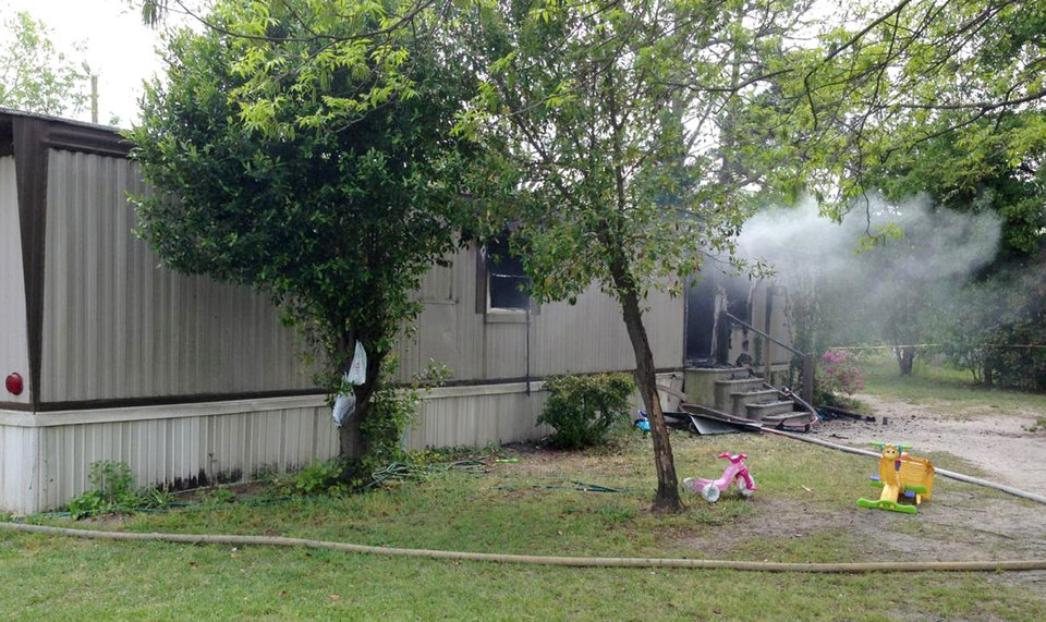 Photo - In this photo provided by the Darlington County Sheriff's office, a mobile home in Florence, S.C. smolders after a fire Wednesday, April 24, 2013.  Four children died in the fire, their bodies discovered by firefighters shortly after they put out the flames, an official said. (AP Photo/Darlington County Sheriff via The Morning News)