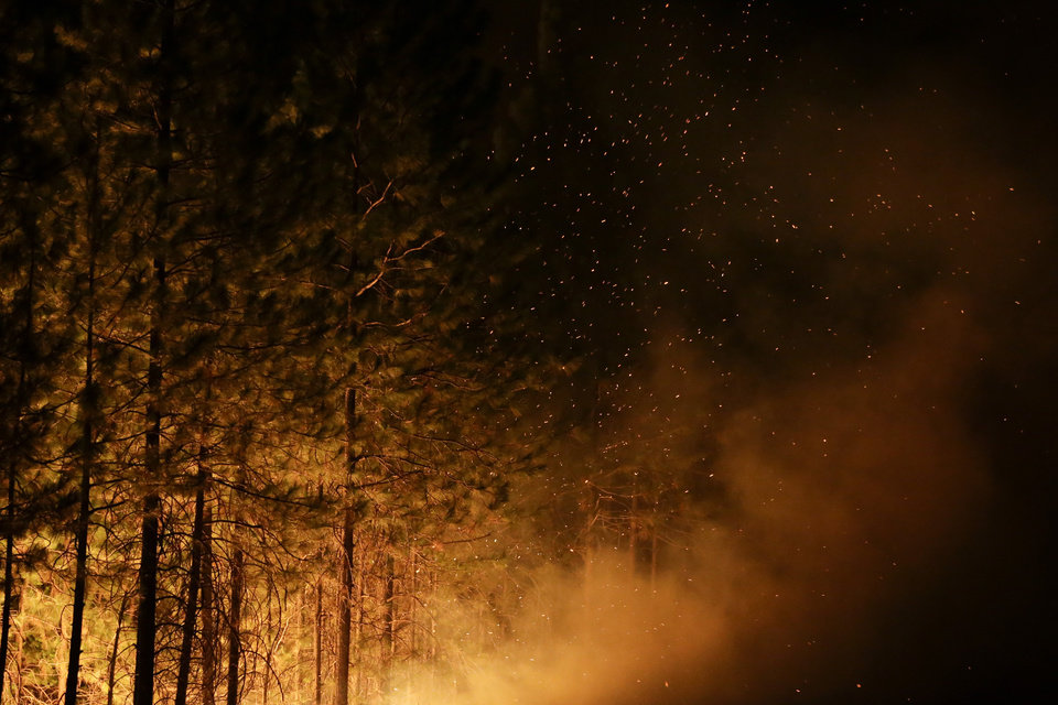 Photo - Embers from burning trees fill the air as firefighters continues to battle the Rim Fire near Yosemite National Park, Calif., on Sunday, Aug. 25, 2013. Fire crews are clearing brush and setting sprinklers to protect two groves of giant sequoias as a massive week-old wildfire rages along the remote northwest edge of Yosemite National Park. (AP Photo/Jae C. Hong)