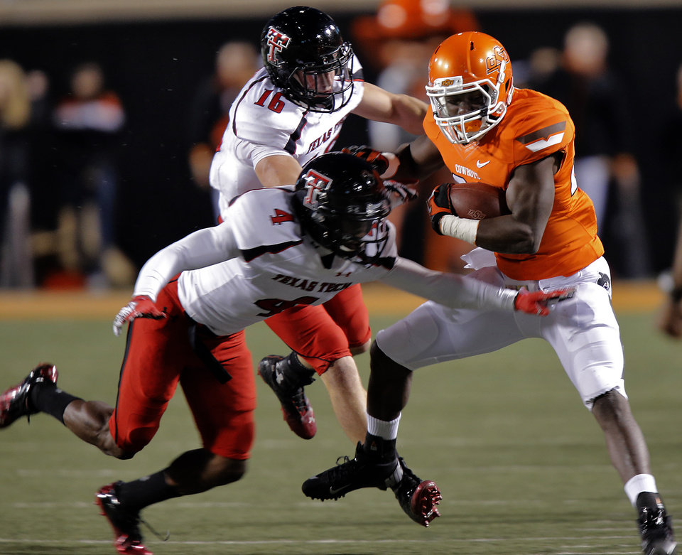 Texas Tech\'s Cody Davis (16) and Derrick Mays (4) bring down Oklahoma State\'s Desmond Roland (26) during the college football game between the Oklahoma State University Cowboys (OSU) and Texas Tech University Red Raiders (TTU) at Boone Pickens Stadium on Saturday, Nov. 17, 2012, in Stillwater, Okla. Photo by Chris Landsberger, The Oklahoman