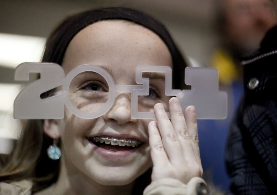 Miah Lingelbach, 12, of Edmond, Okla., laughs as she puts on 2011 glasses on during Opening Night at the Cox Convention Center, Friday, Dec. 31, 2010, in Oklahoma City. Photo by Sarah Phipps, The Oklahoman