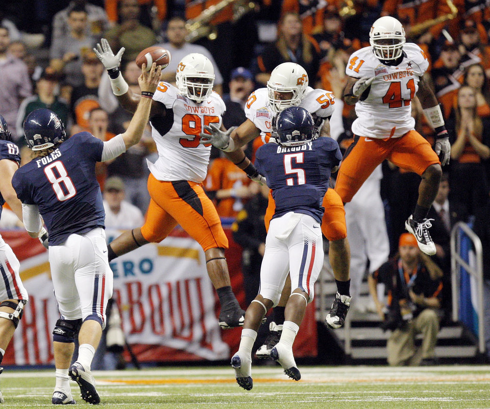 Photo - OSU's Chris Donaldson (95), Jamie Blatnick (50) and Orie Lemon (41) defend a pass by Arizona quarterback Nick Foles (8) next to Nic Grisby (5) in the first quarter during the Valero Alamo Bowl college football game between the Oklahoma State University Cowboys (OSU) and the University of Arizona Wildcats at the Alamodome in San Antonio, Texas, Wednesday, December 29, 2010. Photo by Nate Billings, The Oklahoman