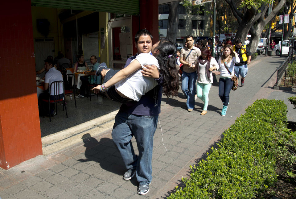 Photo - A woman is carried at the Juarez neighborhood after a strong earthquake jolted Mexico City, Friday, April 18, 2014. The powerful magnitude-7.2 earthquake shook central and southern Mexico but there were no early reports of major damage or casualties. (AP Photo/Eduardo Verdugo)