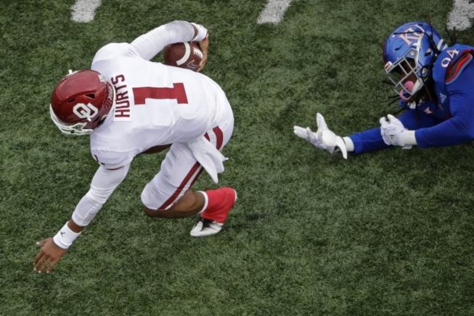 Photo -  Oklahoma quarterback Jalen Hurts gets past Kansas defensive end Codey Cole III during Saturday's game in Lawrence, Kan. [AP Photo/Charlie Riedel]