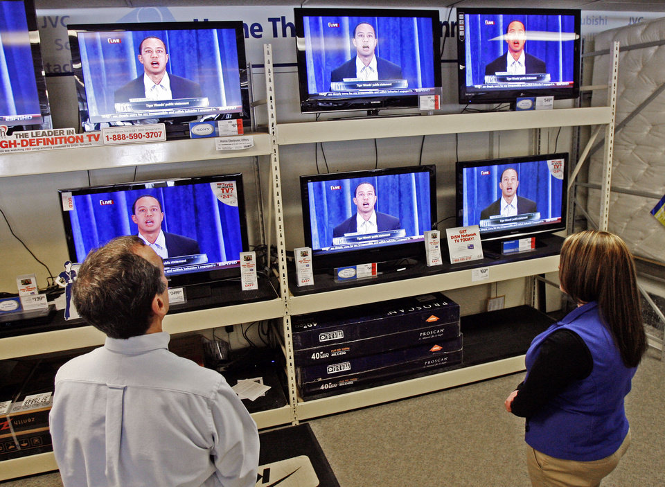 Photo - Owner Louis Lacroix and employee Caitlyn Lacroix stop to watch Tiger Woods on television at the Sears store in Berlin, Vt., Friday, Feb. 19, 2010. Tiger Woods has apologized for having affairs and says he is unsure when he will return to competitive golf.  Woods talked for more than 13 minutes Friday from the clubhouse at the TPC Sawgrass, home of the PGA Tour. (AP Photo/Toby Talbot) ORG XMIT: MR101