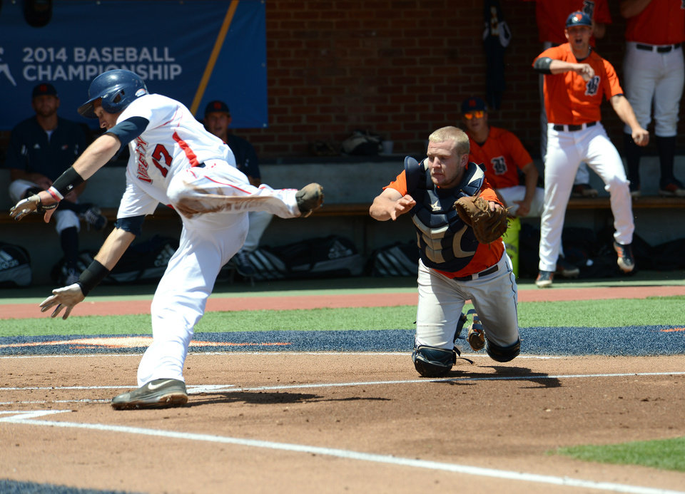 Photo - Liberty's Ashton Perritt, left, avoids the tag of Bucknell's Jon Mayer and scores during the first inning of an NCAA college baseball regional tournament game in Charlottesville, Va., Saturday, May 31, 2014. (AP Photo/Pat Jarrett)