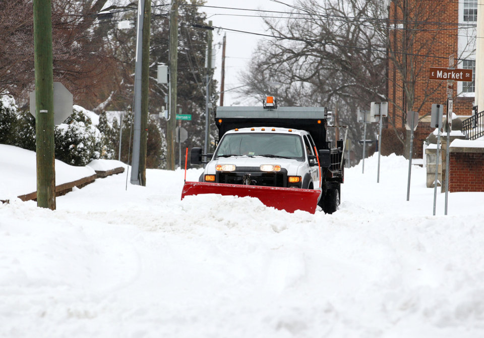 Photo - A plow clears snow along 2nd Street NE at Market Street after a snow fall on Thursday morning, Feb. 13, 2014, in Charlottesville, Va. (AP Photo/The Daily Progress, Ryan M. Kelly)