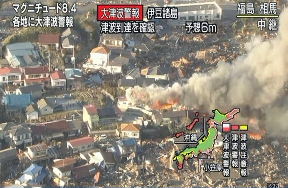 Photo - In this image taken from NHK television, smokes rise from houses in Soma, Fukushima, northern Japan Friday, March 11, 2011 after an earthquake. Japan was struck by a magnitude-8.8 earthquake off its northeastern coast Friday, triggering a 13-foot (4-meter) tsunami that washed away cars and tore away buildings along the coast near the epicenter. (AP Photo/NHK) JAPAN OUT, TV OUT, NO SALES, ONLINE OUT, EDITORIAL USE ONLY ORG XMIT: TOK813