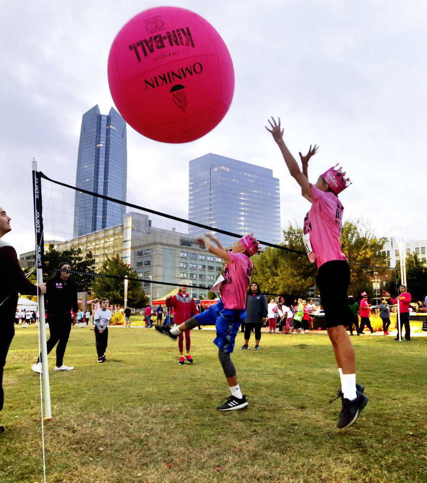 Photo -  Participants play Big Pink Volleyball, courtesy of the University of Central Oklahoma, as they gather in front of the Civic Center before the Susan G. Komen Race for the Cure on Saturday. [PHOTO BY STEVE SISNEY, THE OKLAHOMAN]